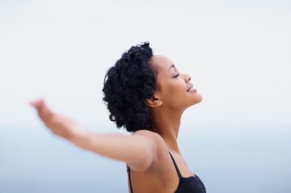 Happy and healthy black young woman relaxing with open arms outdoors